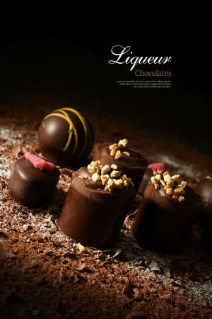 chocolate sprinkles: Creatively lit dark liqueur chocolates against a dark background. Copy space. Stock Photo
