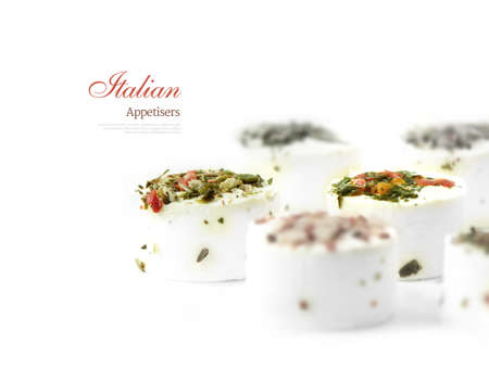 comprising: Popular Italian soft cheese appetizer canapes with mixed toppings comprising of tomato, basil, olives and onion against a white background. Selective focus. Copy space.