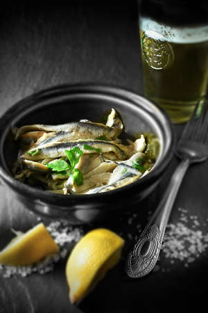 differential focus: Spanish boquerones in olive oil in a rustic setting with differential focus shot in natural light. Copy space.