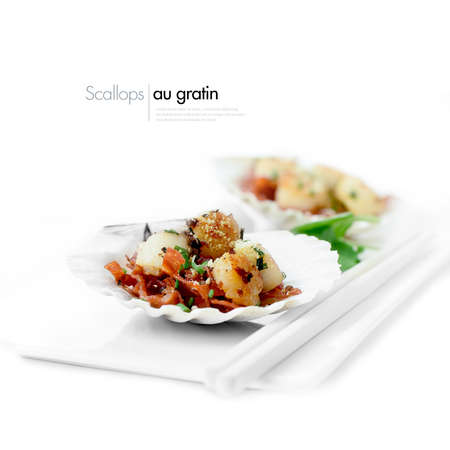 gourmet food: Delicious scallops au gratin starter dish against a white background served with watercress salad, Parmesan cheese and chorizo sausage. Copy space. Stock Photo
