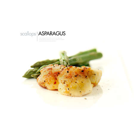 seared: Pan seared scallops with fresh steamed asparagus against a white background. Copy space.