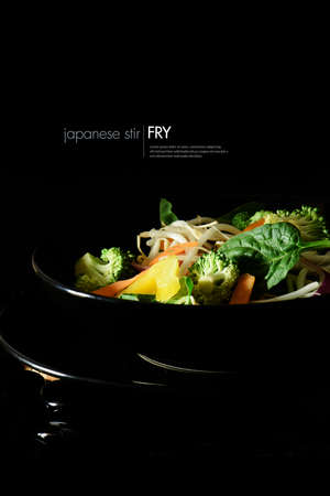 Creatively lit Japanese stir fry vegetables ready for cooking against a black background. Copy space.