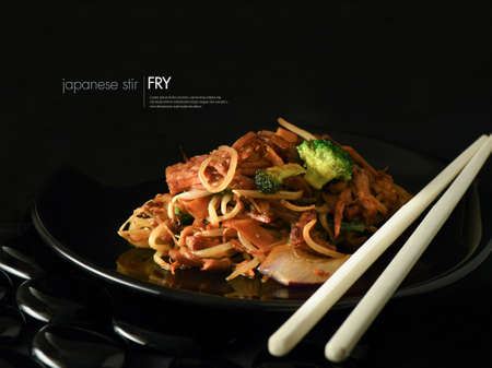Creatively lit Japanese stir fry against a black background. Copy space.