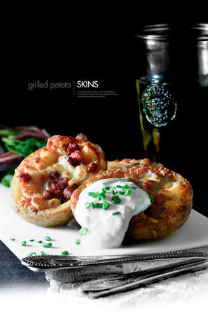 Delicious grilled potato skins with melted cheese and bacon toppings. Soured cream with chives dressing and a cold beer