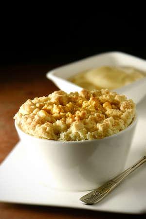 custard slices: Delicious apple crumble in a white ramekin with Devon custard in background. Copy space.