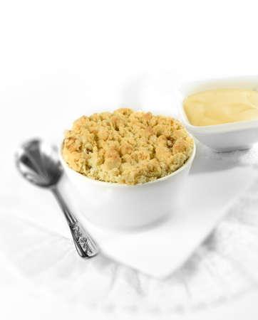 ramekin: Delicious apple crumble in a white ramekin with Devon custard in background