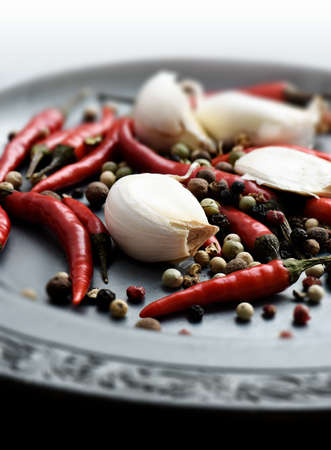 piri: Bird Eye Chillies and garlic cloves scattered on a pewter plate with peppercorns with a shallow depth of field. Copy space. Stock Photo