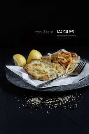 thin shell: Classic Coquilles St. Jacques plated and styled with skinny fries and lemon garnish against a black background. Copy space.