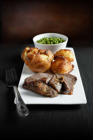 roast potatoes: A curated image of topside roast beef, roast potatoes and traditional Yorkshire pudding in a gourmet setting against a dark background with copy space. Concept image for a Sunday lunch menu design. Stock Photo