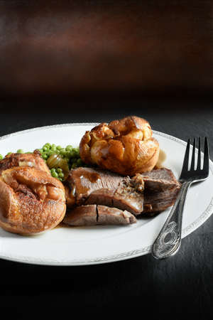 A curated image of topside roast beef, roast potatoes and traditional Yorkshire pudding in a restaurant setting against a dark background with copy space. Concept image for a Sunday lunch menu design.