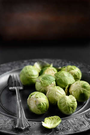 phobia: Raw brussel sproats in a rustic, farmhouse setting against a dark background. Differential focus and copy space. Ideal image for seasonal stories and blogs about sprouts at Christmas and Thanksgiving.