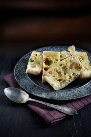 pewter: Tomato and Basil Olive Oil Ciabatta bread in a rustic setting against a dark background. Copy space. Stock Photo
