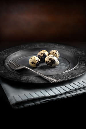 pewter: Farm Quails Eggs on an old pewter plate against a rustic background with selective focus and diffused natural light. A different type of concept image for Easter or pension financial investments.  Copy space. Stock Photo