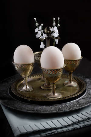egg cups: Victorian Easter breakfast theme, genuine duck eggs in antique Victorian egg cups with white Spring flowers aganst a dark background. An unusual concept image for Easter or pension funds. Copy space.