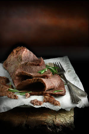 menu background: A curated image of perfectly cooked prime topside roast beef, sliced and ready to eat against a dark, rustic background with copy space. Concept image for a restaurant Sunday lunch menu cover design. Stock Photo