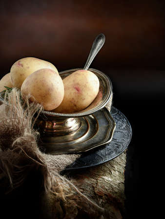 A curated image of fresh uncooked organic potatoes in an antique Victorian serving dish with hessian cloth against a dark, rustic background with copy space. Concept image for a restaurant menu cover design.