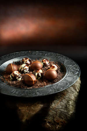 Creatively lit dark liqueur chocolates against a dark rustic background with copy space. Concept image for a restaurant dessert menu cover design. Stock Photo