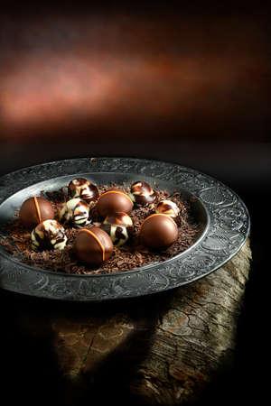 Creatively lit dark liqueur chocolates against a dark rustic background with copy space. Concept image for a restaurant dessert menu cover design. Standard-Bild