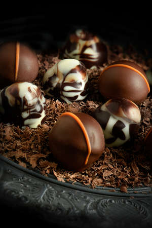lit image: Creatively lit dark liqueur chocolates against a dark rustic background with copy space. Concept image for a restaurant dessert menu cover design. Stock Photo