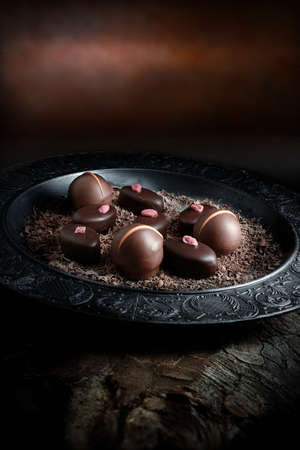 dessert: Creatively lit dark liqueur chocolates against a dark rustic background with copy space. Concept image for a restaurant dessert menu cover design. Stock Photo