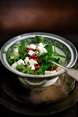 Creatively lit freash and healthy Greek feta cheese and pomegranate rocket salad against a dark rustic background with copy space. Concept image for a restaurant menu cover design. photo