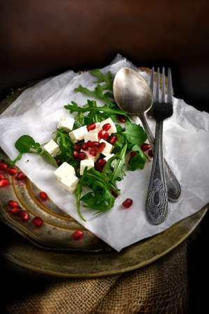 Creatively lit fresh and healthy Greek feta cheese and pomegranate rocket salad against a dark rustic background with copy space. Concept image for a restaurant menu cover design. photo