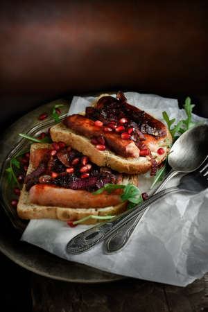 Creatively lit grilled pork sausage and caramalised red onion sandwich with rocket and pomegranate against a dark rustic background with copy space. Concept image for a restaurant menu cover design. photo
