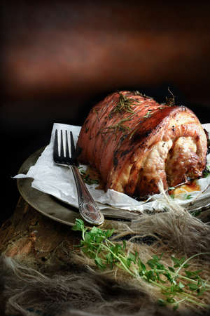 Creatively lit pork roast joint with rosemary, thyme and lemon against a  rustic background with copy space. The perfect image for your Sunday lunch menu cover design. Stock Photo - 38312577
