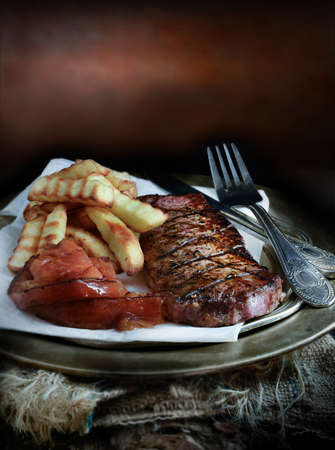 selectively: Close-up grilled sirloin steak, French fries and grilled tomatoes. Selectively lit against a rustic background. Perfect for your cover menu design. Copy space.