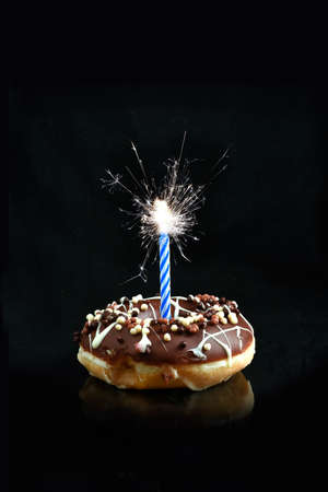 smothered: Creative image of a chocolate smothered donut with blue candle sparkler against a black background with copy space. Concept image for celebrations or birthdays.