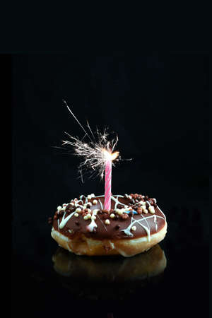 smothered: Creative image of a chocolate smothered donut with pink candle sparkler against a black background with copy space. Concept image for celebrations or birthdays.
