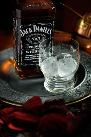 daniels: NOTTINGHAM, UNITED KINGDOM - APRIL 30, 2015: Jack Daniels whiskey bottle and glass with ice. Jack Daniels is a brand of sour mash Tennessee whiskey and the highest selling American whiskey in the world.