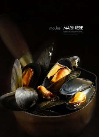 Creatively lit and focused Moules Mariniere, mussels steamed in white wine and garlic cream sauce in a rustic setting against a dark background. Copy space. Stock Photo