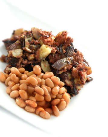 nosh: Image of corn beef hash, fried, corned beef, onions and potatoes with baked beans in tomato sauce against a white background. Classic comfort food nosh. Copy space.