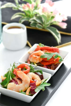 saki: Fresh Japanese cuisine, prawns and rocket salad leaves with moist red peppers. Sake and authentic Japanese flowers in the background.
