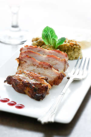 stuffing: Plated freshly grilled pork bellies with sage and onion stuffing and raspberry coulis in a restaurant setting against a bright background. Copy space. Stock Photo