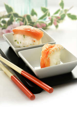 accommodate: Fresh Japanese sushi in trational asian table setting with salmon and shrimp delicacies, chop sticks and rice. Shot against a bright background to accommodate copy space.