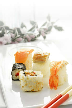 accommodate: Fresh Japanese sushi in traditional asian table setting with salmon and shrimp delicacies, chop sticks and rice. Shot against a bright background to accommodate copy space.