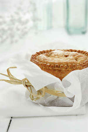 british food: Fresh home baked pork pie with shortcrust savoury pastery wrapped in greaseproof paper tied with raffia against a bright, light background. Concept image for buffet food. Copy space.