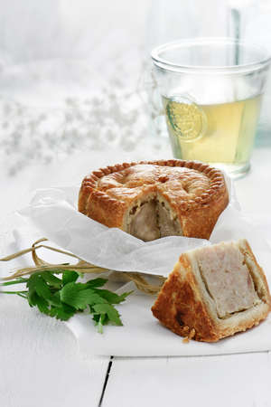 cur: Fresh home baked pork pie with shortcrust savoury pastry wrapped in greaseproof paper tied with raffia against a bright, light background. Concept image for buffet food. Copy space.