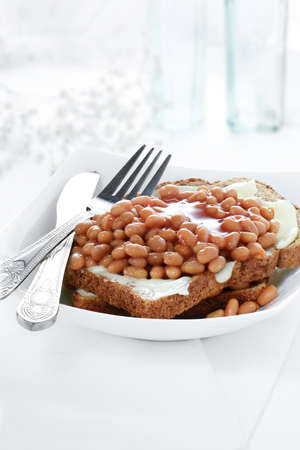 beans on toast: Classic baked beans on toast meal in an elegant setting against a light, bright background with copy space.
