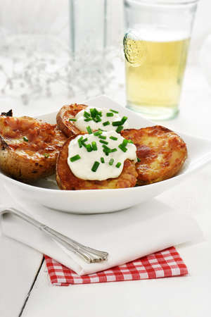 soured: Freshly grilled bacon and cheddar cheese potato skins ozzing with soured cream against white. The perfect image for a bistro or restaurant menu and advertisement. Copy space.