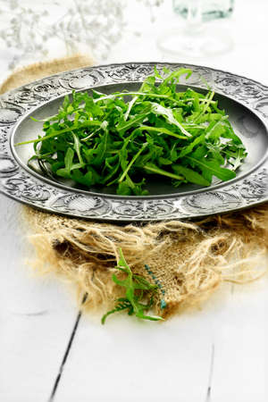 rukola: Fresh rocket leaf salad on an antique pewter plate on hessian fabric in a rustic setting against a light, bright background. Concept image for healthy eating. Copy space.