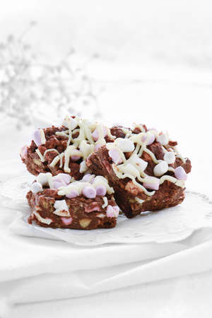 Delicious Rocky Road Belgium chocolate and marsh mellow chunks against white lace and muslin. Concept image for wedding favors or desserts. Copy space.
