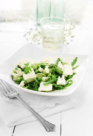 feta cheese: Greek feta cheese chunks with rocket salad and edamame beans with olive oil dressing against a white background. Copy space. Stock Photo