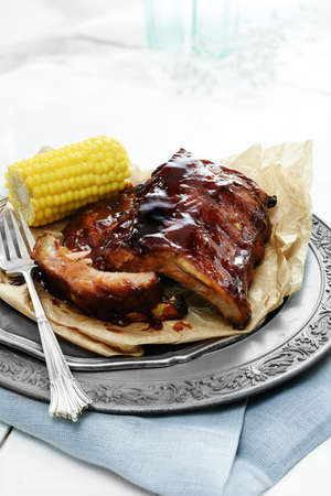 smothered: Grilled BBQ pork ribs stacked on an antique plate against a light, bright background smothered in a spicy, smoky sauce. The perfect image for your bistro menu cover design. Copy space.