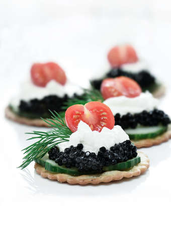 Delicious cream cheese, cucumber and caviar canapes against white. Copy space. photo