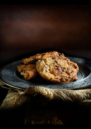 Home baked double chocolate chip cookies in a rustic, antique setting with creative lighting with generous copy space. Concept image for your dessert menu cover design. Stock Photo