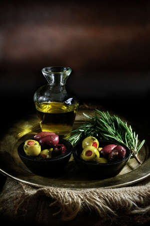creatively: Rustic styled image of classic italian food ingedients against a rustic and creatively lit background. Olive oil, stuffed Pimento green olives and pitted Kalamata olives with rosemary herbs.