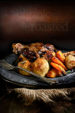 lamb shank: Roast lamb shank with roasted potatoes and carrots styled in a rustic setting with generous copy space. Concept image for home cooking or your bistro or restaurant menu cover design.